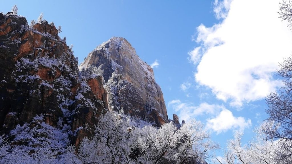 snowy cliff with cloud covering sun and blue sky in background